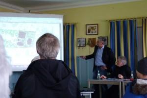 Der Architekt Herr Göttsch (stehend) stellt einen Entwurf der Häuser vor